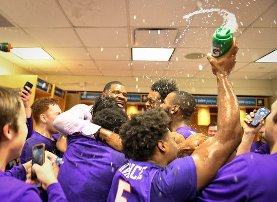 Evansville head coach Walter McCarty celebrates with the Aces in the locker room after the gameas the University of Evansville Purple Aces defeat the number one ranked Kentucky Wildcats 67-64 at Rupp Arena in Lexington Tuesday evening, November 12, 2019.