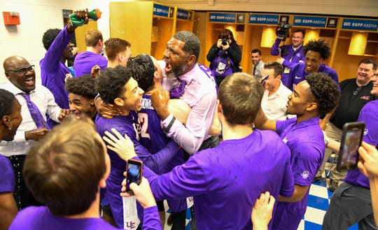 Evansville head coach Walter McCarty celebrate with his team after defeating the number one ranked Kentucky Wildcats at Rupp Arena in Lexington Tuesday evening, November 12, 2019.