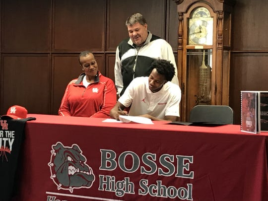 Bosse basketball player Kiyron Powell (right) signs his national letter of intent to play at Houston. Joining him on stage were his mother, Teresa Higgins (left), and coach Shane Burkhart (middle).