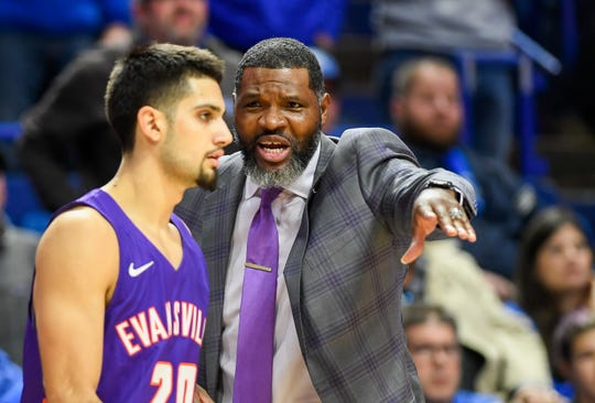 Evansville head coach Walter McCarty talks with Evansville's Sam Cunliffe (20) as the University of Evansville Purple Aces play the number one ranked Kentucky Wildcats at Rupp Arena in Lexington Tuesday evening, November 12, 2019.