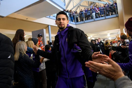 University of Evansville's Sam Cunliffe, center, walks past cheering fans during a pep rally held for his team inside UE's Ridgway University Center in Evansville, Wednesday, afternoon, Nov. 13, 2019. On Tuesday evening, the Purple Aces shocked sports fans across the country by defeating the No.1 ranked University of Kentucky Wildcats 67-64.