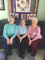 Quilters still share time together. From left are Carol Swope, Mary Widmer and Nancy Early.  Behind them is a quilt made by Swope.