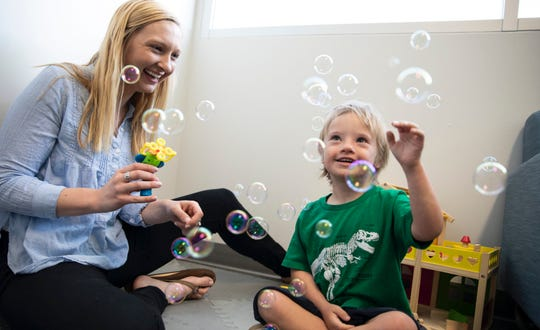 Emily Schworer, lab coordinator at the Developmental Disabilities Research Laboratory, uses bubbles to play with a research participant.