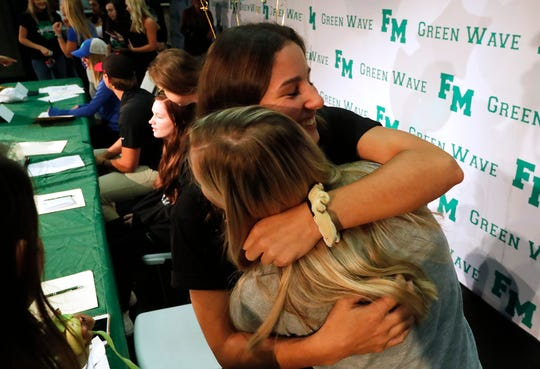Allana Consolazio (USF softball) gets a congratulatory embrace from her friend Maddie Kline during the Fort Myers High School athletic signings ceremony Wednesday afternoon, November 11, 2019.