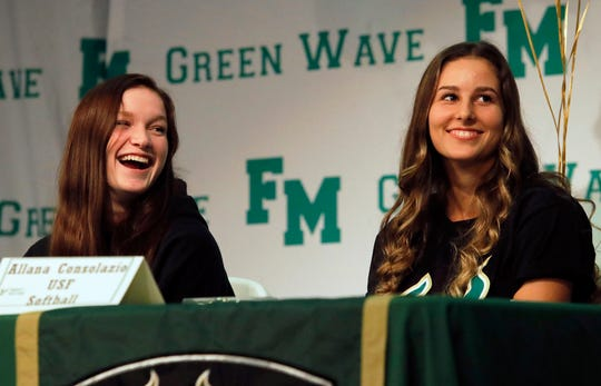 From left, Ryley Topliff (FGCU softball) and Allana Consolazio (USF softball) share a laugh during the Fort Myers High School athletic signings ceremony Wednesday afternoon, November 11, 2019.
