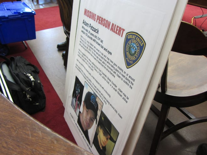A missing person alert poster sits with other evidence at the prosecution's table following opening statements in the trial of Brandon Lee Craft for the murder of Adam Petzack.