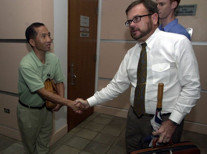 In this July 2001 file photo, slot machine owner Allen Ra, left, is congratulated by his attorney, David Highsmith, after a judge granted the temporary return of gambling machines that were seized. Highsmith, who later was an assistant attorney general, was arrested Aug. 1 in connection with shoving an attorney at the courthouse.