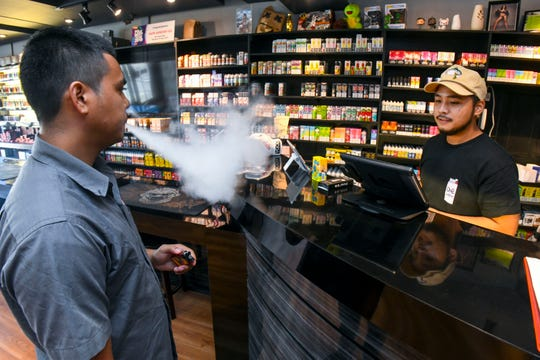 Customer Jason Quiambao, left, exhales vapor as he completes his purchase transaction with store employee, Evan Joel Diras, at the Vape Armory in East Hagåtña on Wednesday, Nov. 13, 2019.