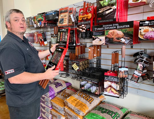 Tracy Hopson of Grills of Mississippi adds merchandise to the wall of grill gadgets at Grills of Mississippi in Ridgeland.