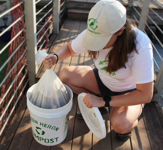Green Heron founder Kat McDearis pulls a full compost bin liner from a bin. She collects compost from residences and businesses on an on-demand basis, replacing the liner each time.