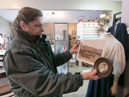 Readying the soon-to-open Rare Findings antique and art store in Genoa Township Wednesday, Nov. 13, 2019, owner Pam Thomas holds a photo of her great grandmother Olive, as well as a group shot of bicyclists including Olive, in front of an outfit Olive wore in the group photo of bicyclists in Woodstock, Vermont in 1916.