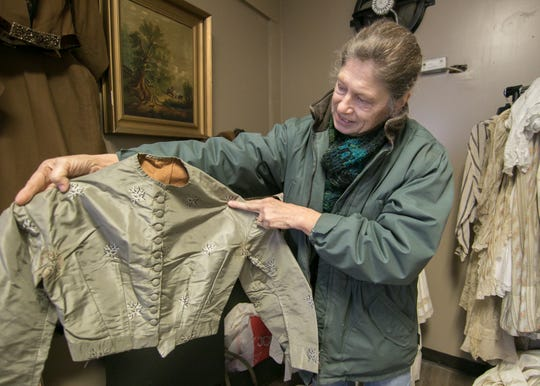 Pam Thomas, owner of Rare Findings in Genoa Township holds a silk top on Wednesday, Nov. 13, 2019 that was passed down from her great-great grandmother, one of a variety of antiques the store will offer.