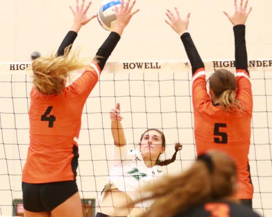 Ashley Brown and Paris Dixon of Brighton go high to block a Novi shot in a regional semifinal volleyball match on Tuesday, Nov. 12, 2019.