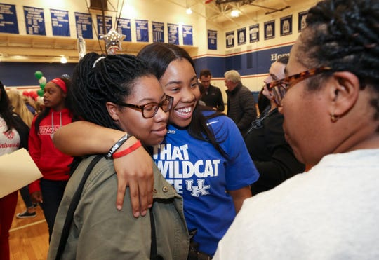Sacred Heart Academy senior Erin Toller, center, embraced her sister Ericka Toller, 23, as their mom Yvette Toller looked on during Signing Day for college bound athletes at the school in Louisville, Ky. on Nov. 13, 2019.  Toller signed to play basketball at the University of Kentucky.