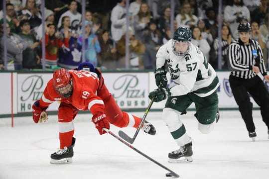 Michigan State defenseman Jerad Rosburg fights for the puck against a Cornell forward. Rosburg, a fifth-year senior, is the anchor of the Spartans' defense.