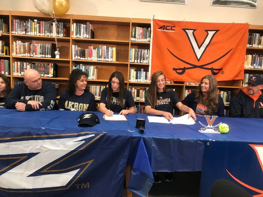 Madison's Leah Boggs, at center right, and Sloan Kiser, center left, sign national letters of intent to play Division I college softball at Virginia and Akron, respectively, on Wednesday afternoon at Madison High School.
