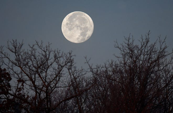 A full frost moon sets in the west Wednesday morning.