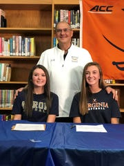 Leagh Boggs, right, and Sloan Kiser pose with Madison head softball coach Tim Niswander after signing to play Division I college softball.