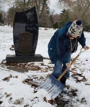 Melissa Dolan of Wauwatosa shovels the walkway of the Garden of Angels at Pinelawn Memorial Park, 10700 W. Capitol Drive, on Nov. 13. Her baby's grave is located nearby. Over 200 vases, including her baby's, was stolen from the cemetery.