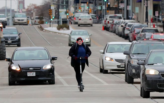 Carrianne Ledvina, of Milwaukee rides a Bird electric scooter down North Broadway Avenue near East Clybourn Street in Milwaukee on Wednesday, Nov. 13, 2019. Ledvinawas headed to class at Milwaukee Institute of Art and Design (MIAD) in Milwaukee.   Photo by Mike De Sisti/Milwaukee Journal Sentinel