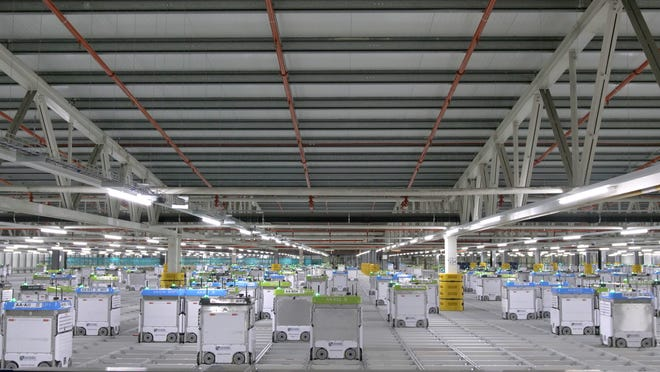 Bots work on a grid at an automated warehouse fulfillment center.  A similar facility is planned for Pleasant Prairie by Kroger and its partner Ocado.
