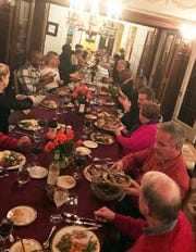 Guests gather at a long table at Heidi Marcelle's house in Shorewood for Thanksgiving dinner. The gathering has grown to include about 25 people, with four turkeys.