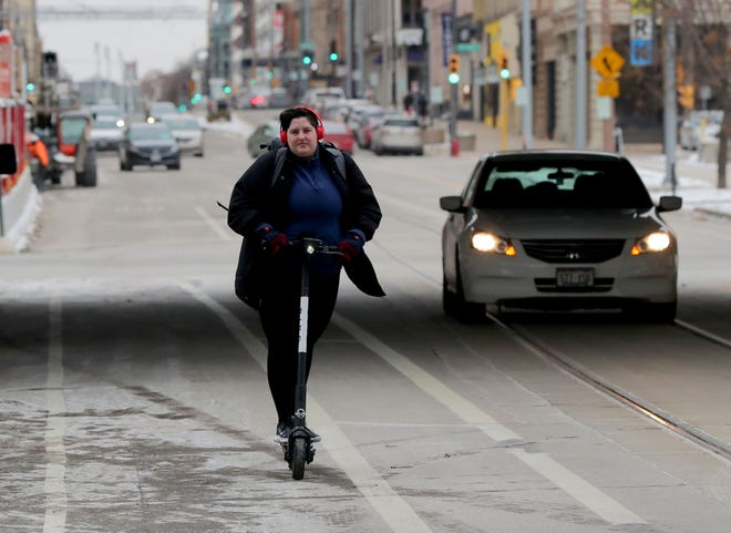 Carrianne Ledvina of Milwaukee rides a Bird electric scooter down North Broadway near East Clybourn Street in Milwaukee on Nov. 13, 2019. Ledvina was headed to class at Milwaukee Institute of Art and Design in Milwaukee.