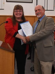 Twin lakes Literacy Council executive director Heather Powell (lefts) accepts a proclamation from County Judge Mickey Pendergrass on Tuesday night at the Baxter County Quorum Court meeting. Pendergrass proclaimed Thursday, Nov. 14 as Twin Lakes Literacy Day as part of Family Literacy Month in Baxter County.