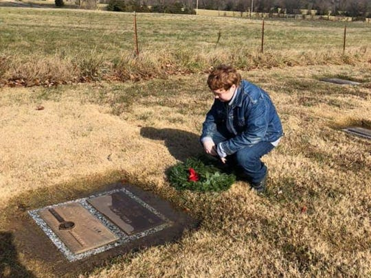 A volunteer with Wreaths Across America places a wreath on the grave of a local veteran during 2018's National Wreaths Across America Day.