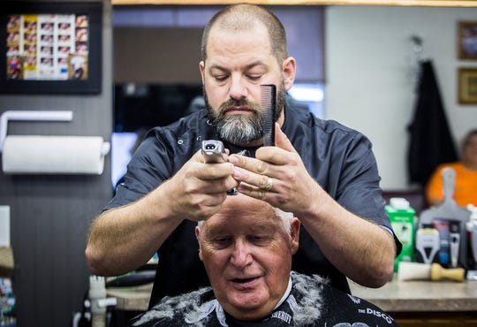 Owner Brian Richards gives a haircut to his mentor, Bob Kibbey, at Maxwell's Barber Shop on Memorial Drive.