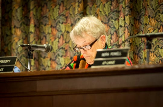 Council member Linda Gregory looks down at the bench as both the public and her fellow council members discuss her censure on the council.