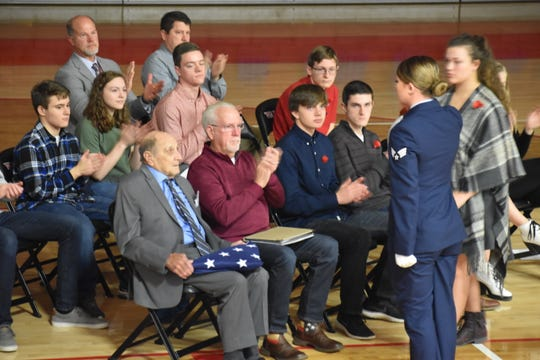 U.S. Marine and World War II veteran Junior Howell is presented a flag of honor by WHS graduate and active duty Sr. Airman Katie Leach on Nov. 11. They are surrounded by members of the WHS AP U.S. History class who organized the 2019 Veterans Day program.