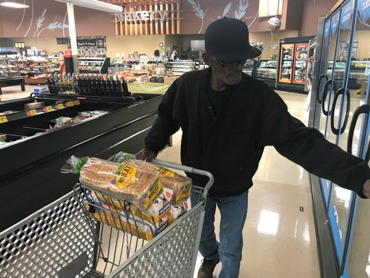 Dewayne McCord, a resident at Franklin Community House, shops at Kroger in Franklin with the help of The Church at West Franklin. He buys items to feed eight men at the home.