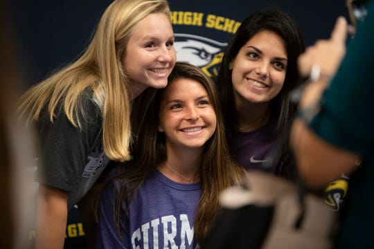 Ashlee Lykins , center, poses for photos with friends shortly after a signing ceremony, Wednesday, Nov. 13, 2019, at Naples High School.