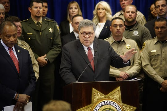 U.S. Attorney General William Barr, center, with other federal and officials, announces that nearly 330 fugitives suspected of violent crimes have been arrested as part of a crime-fighting initiative in New Mexico, at a news conference at the office of the Bernalillo County Sheriff in Albuquerque, N.M., Tuesday, Nov. 12, 2019. Barr was in Albuquerque to highlight the results of Operation Triple Beam, a program that has been conducted in numerous U.S. cities and has led to hundreds of arrests.