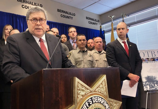 U.S. Attorney General William Barr, left, with other federal and officials, announces that nearly 330 fugitives suspected of violent crimes have been arrested as part of a crime-fighting initiative in New Mexico, at a news conference at the office of the Bernalillo County Sheriff in Albuquerque Tuesday, Nov. 12, 2019. Barr was in Albuquerque to highlight the results of Operation Triple Beam, a program that has been conducted in numerous U.S. cities and has led to hundreds of arrests.