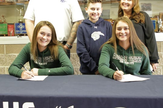 Piedra Vista's Makenzie Bayless, left and Taylor Bayless, right, sign their National Letters of Intent on Wednesday to continue their softball careers at NCAA Division II Adams State University.