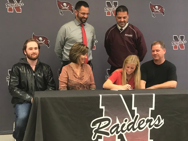 Navarre's Hailey Bastian (front row, center right) signs a soccer scholarship with South Alabama with family, coaches and administrators at Navarre High on Nov. 13, 2019.