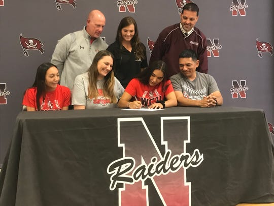 Navarre softball pitcher Allison Gutierrez (front row, center right) signs an athletic scholarship with William-Carey University at Navarre High on Nov. 13, 2019.
