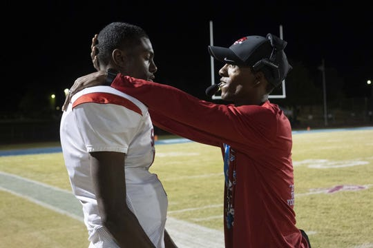 South Mountain coach Mark Carter talks to quarterback Amier Boyd during a game against Betty H. Fairfax on Oct. 18.