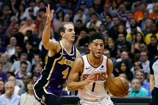 Phoenix Suns guard Devin Booker (1) drives past Los Angeles Lakers guard Alex Caruso in the second half during an NBA basketball game, Tuesday, Nov. 12, 2019, in Phoenix. (AP Photo/Rick Scuteri)