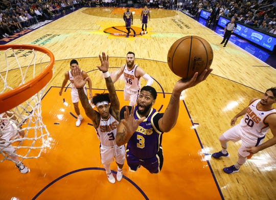 Los Angeles Lakers forward Anthony Davis (3) drives to the basket against Phoenix Suns forward Kelly Oubre Jr. (3) in the first half on Nov. 12, 2019 in Phoenix, Ariz.
