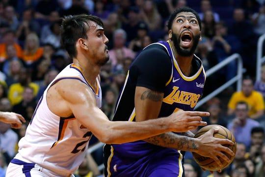 Los Angeles Lakers forward Anthony Davis (3) drives on Phoenix Suns forward Dario Saric in the first half during an NBA basketball game, Tuesday, Nov. 12, 2019, in Phoenix. (AP Photo/Rick Scuteri)