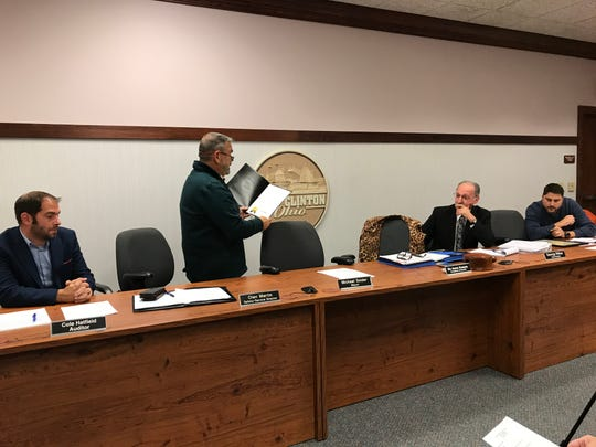 Safety-Service Director Olen Martin reads an official state senatorial citation from Sen. Theresa Gavarone commending outgoing city law director George Wilber for his 40 years of dedicated civil service to Port Clinton.
