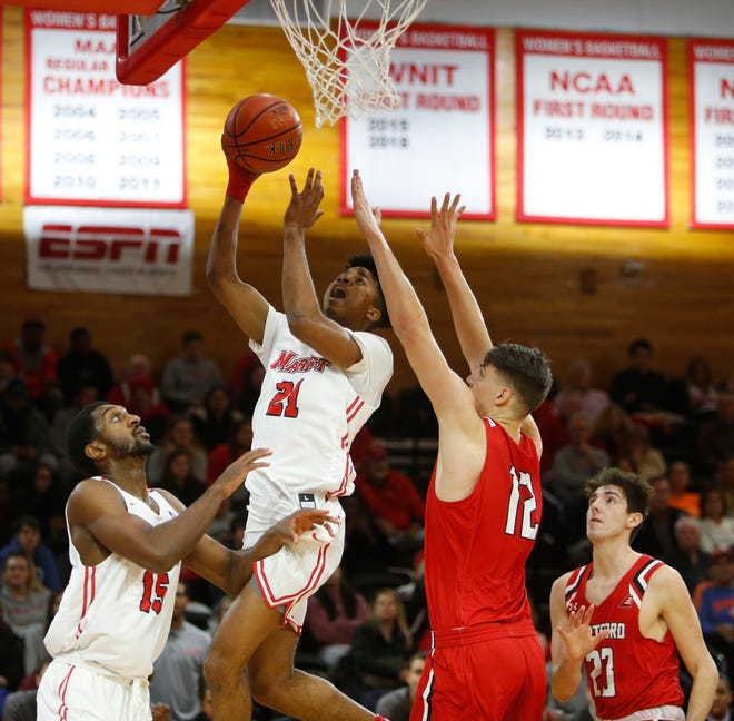 Marist's Tyler Saint-Furcy takes a jump shot as Hartford's Miroslav Stafl covers him during Tuesday's home opener on November 12, 2019.