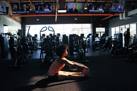 Cindy Alvarez of Jackson, Miss., stretches on the workout mat at Fondren Fitness, while various television screens show different networks views of the Trump impeachment hearings as well as HGTV and ESPN programming, Wednesday, Nov. 13, 2019. (AP Photo/Rogelio V. Solis)
