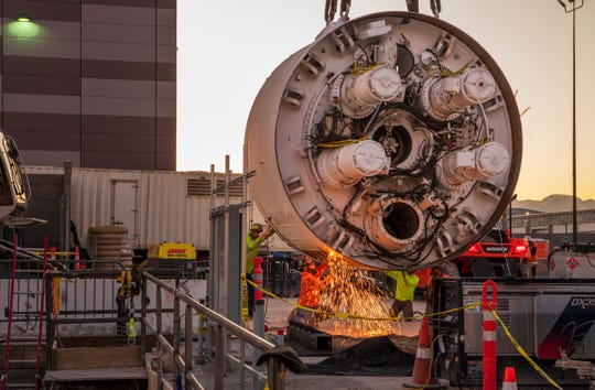 Workers cut the storage rack from the base of the drill head  as the Boring Company prepares to lower the drill head for the People Mover tunnel which will connect convention halls as part of the LVCCD Phase 2 construction in the Red Lot east of the south Hall at the Las Vegas Convention center on Monday, Oct. 28, 2019.