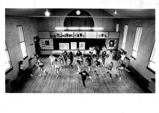 Sister Mary Ellen Campbell, in front wearing a black leotard, leads a 10th grade dance class in a former chapel at Nazareth Academy in 1984.