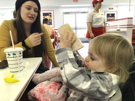 Caroline McCarley watches her nearly 2-year-old daughter Amelia finish a Neopolitan milkshake at the new In-N-Out Burger in south Redding on Tuesday, Nov. 12, 2019. McCarley and Amelia were two of the first customers when In-N-Out opened its second location in Redding.