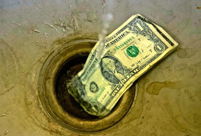 Water drips on dollar bills in this Wednesday, Nov. 13, 2019 photo illustration.